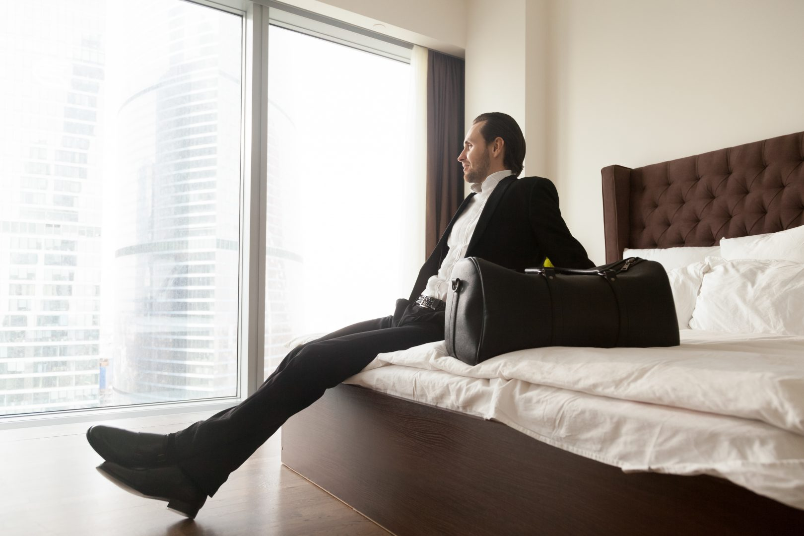 Relaxed businessman with luggage bag sitting on bed in luxurious hotel room, looking towards window. Smiling entrepreneur in suit rests after long business trip, looking forward to unpack and relax.